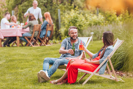 Smiling friends cheering during meeting while relaxing on sunbeds in the garden