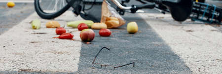 Glasses, groceries and a bicycle on an empty road crossing - panorama of a dangerous car accident concept Stock Photo