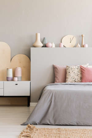 Pink pillows on grey bed with headboard in bedroom interior with rug and cabinet. Real photo