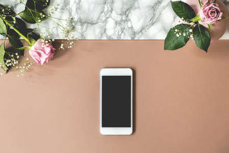 Two pink roses on top view photo of marble table with mockup phone and empty space for your product Stock fotó