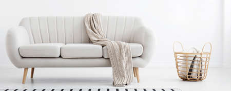 Blanket thrown on light grey sofa standing in the real photo of bright living room interior with wicker basket