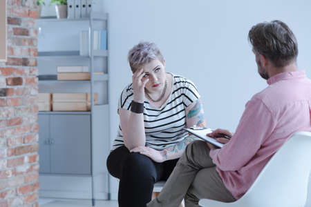 Rebellious young girl with lack of self-acceptance and drug addiction problem during an individual psychotherapy session with an intervention specialist. Stock Photo - 106089450