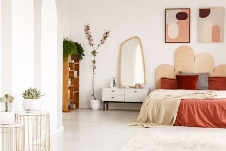 Posters above red bed with blanket in spacious bedroom interior with mirror and plants. Real photo