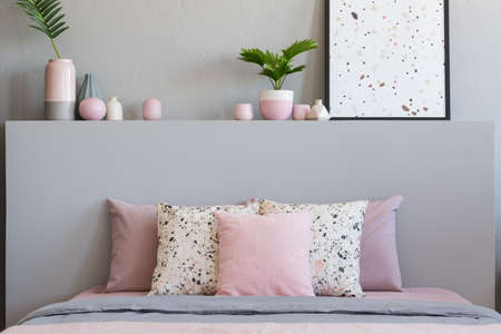Pink and patterned pillows on bed with headboard in grey bedroom interior with poster. Real photo Banque d'images