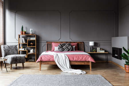 Patterned armchair in spacious grey bedroom interior with pink wooden bed and carpet
