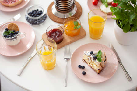High angle on table with dessert, orange juice and marmalade during breakfast. Real photo