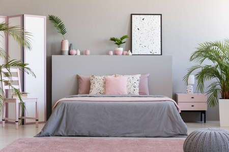 Poster on grey bedhead in bedroom interior with pink pillows on bed next to chair. Real photo Stockfoto