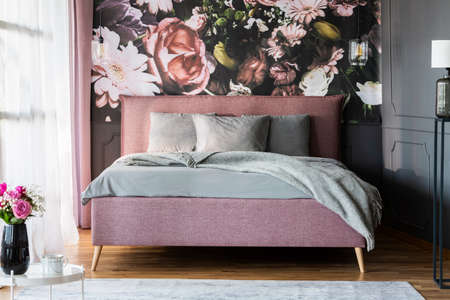 Grey sheets on pink bed in feminine bedroom interior with flowers print on the wall. Real photo