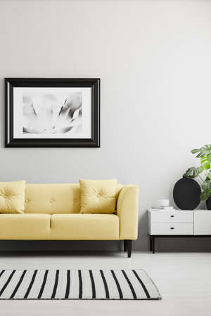 Poster above yellow sofa in minimal grey living room interior with rug and cupboard. Real photo Stock Photo