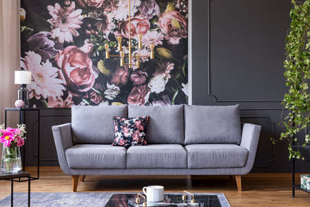 Grey lounge with patterned cushion in real photo of dark living room interior with floral wallpaper, molding on the wall and gold lamp