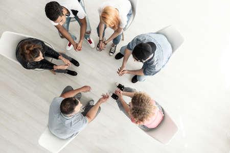 Bovenaanzicht op groep tieners zittend in een kring tijdens overleg met hulpverlener