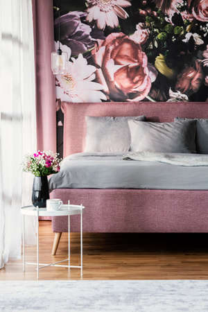Flowers on white table in pink and grey bedroom interior with pillows on bed. Real photo Stock fotó