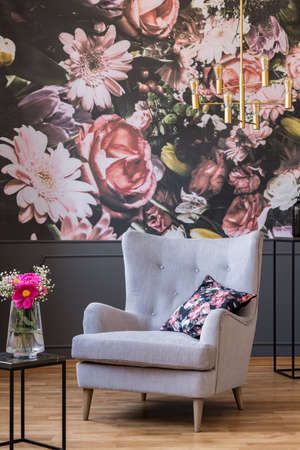 Grey armchair with cushion standing in real photo of dark living room interior with floral wallpaper and gold lamp