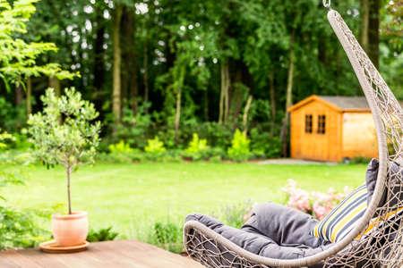Hangstoel met gestreept kussen geplaatst op terras buiten het huis met tuin. Onscherpe achtergrond