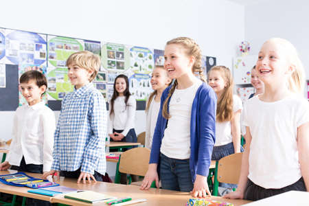 Smiling girls and boys singing song in the classroom during music lesson