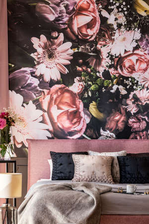 Flowers wallpaper above pink bed with grey and black pillows in feminine bedroom interior. Real photo
