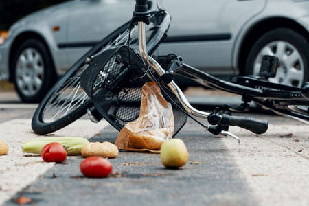 Low angle on groceries and bike after car accident with drunk driver