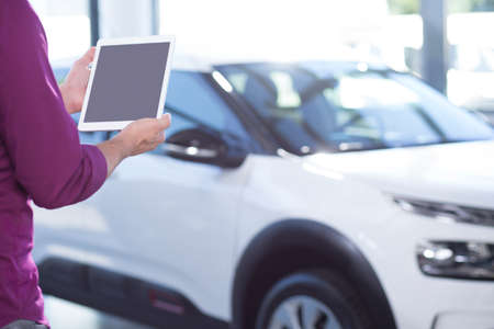 Mockup of tablet of car seller in dealing salon with extravagance vehicles