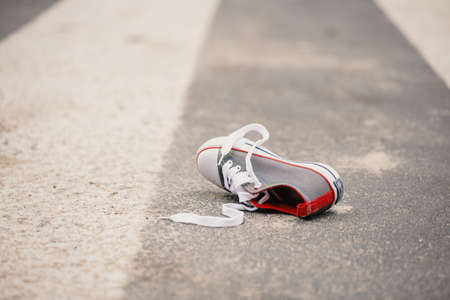 Child's shoe on the street after dangerous traffic incident