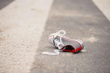 Zapato de niño en la calle después de un incidente de tráfico peligroso