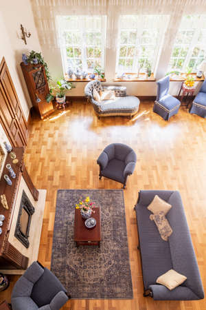 Top view of a classic, blue living room interior with a sofa, armchairs, fireplace, windows and wooden parquet