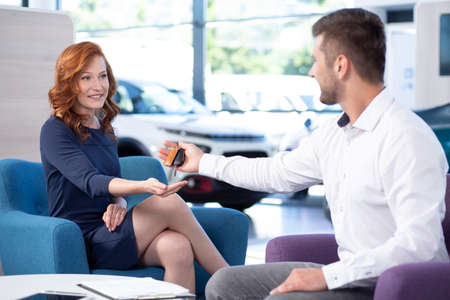 Professional car dealer giving keys to woman in exclusive salon with vehicles