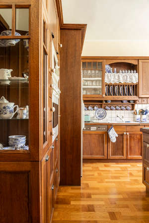 Real photo of a kitchen interior with wooden cupboards and floor