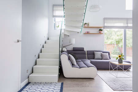 Large, modern sofa in a white living room interior with natural light and stylish staircase with glass barricade Reklamní fotografie