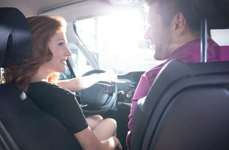 Happy woman during test drive in exclusive car with seller