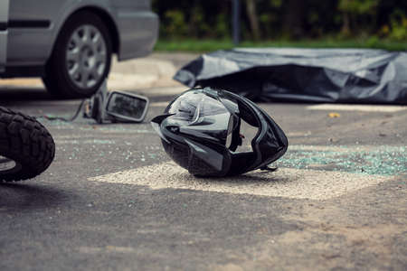 Black motorcycle helmet on the street after collision with a car