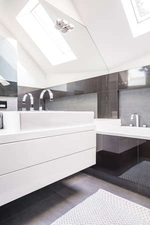 Big mirror by a modern, white washbasin cabinet in a fancy bathroom interior with reflective, black tiles and a roof window