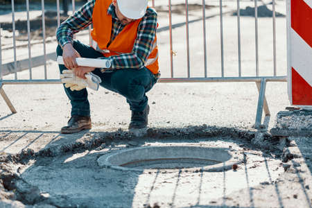 Engineer in reflective vest standing near a hole in the road during carriageway work Stock Photo