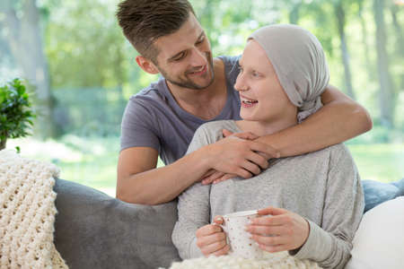 Happy husband hugging his wife recovering from chemotherapy for leukemia Stock fotó
