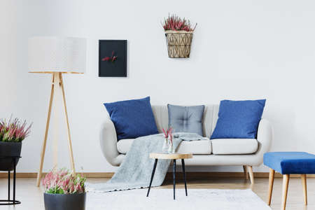 Blue cushions on settee next to a wooden lamp in living room interior with heathers and stool Stock Photo