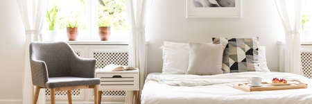 Grey armchair standing by the bedside table with open book in the real photo of white bedroom interior with double bed with cushions and white sheets and plants on windowsill Stock Photo
