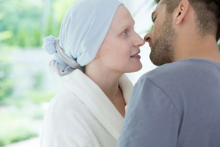 Close-up of sick wife with ovarian cancer looking at her husband with love