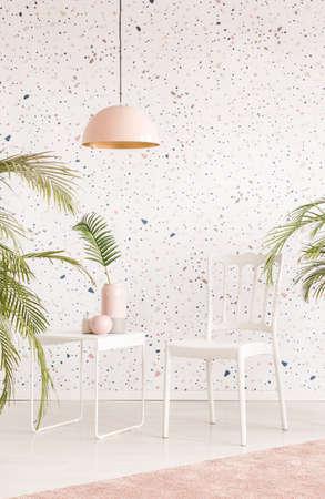 Roze lamp boven witte stoel en tafel in lichte woonkamer interieur met planten. Echte foto Stockfoto