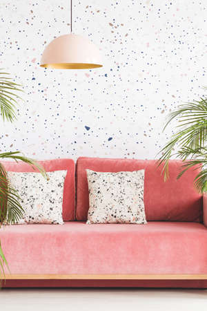 Pastel lamp above pink couch with patterned cushions in living room interior. Real photo