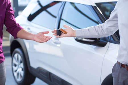 Close-up of car sellers hand with keys and buyer after transaction in the salon Stockfoto