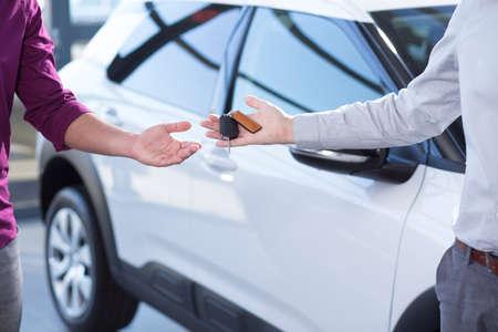 Gros plan de la main du vendeur de voiture avec les clés et l'acheteur après transaction dans le salon