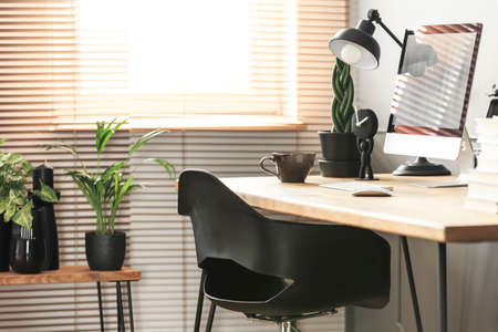 Real photo with close-up of home office corner in living room interior with fresh plants and window with blinds
