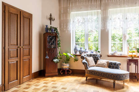 Real photo of a living room interior with a chaise longue, porcelain vases, wooden door and windows with curtains