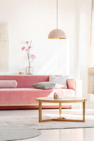 Retro style, millennial pink pendant lamp above a simple, wooden coffee table in a sunny, white living room interior with patterned pillows on a velvet sofa Foto de archivo - 106142393