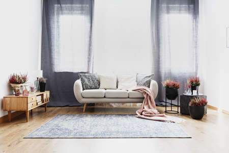 Pink blanket on couch near heathers and wooden cupboard in living room interior with drapes