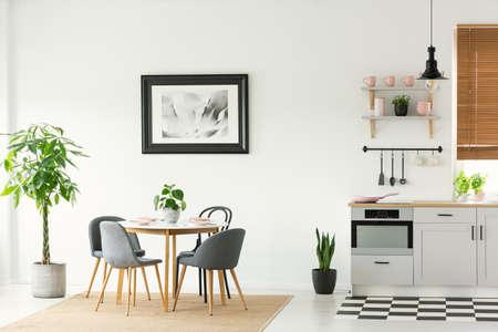 Ingelijste foto op een witte muur in een open ruimte eetkamer en keuken interieur met moderne, houten meubels en planten