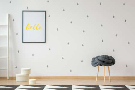 Poster on wallpaper in teenager's room interior with stool and geometric carpet. Real photo with a place for your desk Reklamní fotografie - 106142408