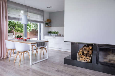 Modern fireplace and wood in a spacious dining room interior with white chairs by a wooden table and big windows Stockfoto