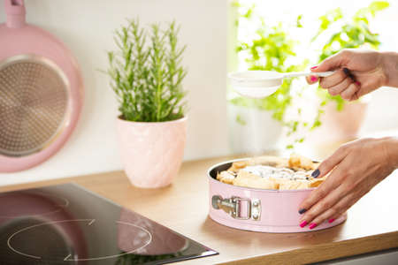 Womans hands sifting sugar on a sponge cake in a pastel pink springform pan in a bright kitchen interior