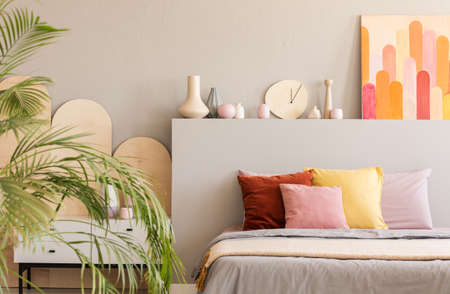 Colorful painting above bed with cushions in grey bedroom interior with palm. Real photo