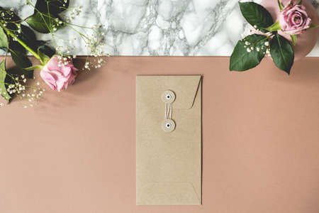 High angle of dirty pink and marble desk with fresh roses, paper envelope and empty spaces for your notebooks and pens Stock Photo